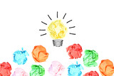 Generating great idea with multiple colorful crumpled pieces of paper around a yellow bright light bulb shaped paper on white background