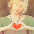 Girl blonde teenager in green blouse showing hands gesture heart