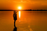 Woman is holding sun in water at sunset
