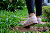 Girl with sneakers walking in park background