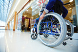Disabled shopper moving in wheelchair along departments in the mall