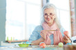 Grey-haired woman painting Easter eggs