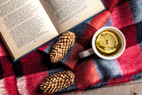 cup of hot tea with lemon on wool shawl with opened book