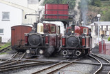 Narrow Gauge Steam Locomotives Talesin and David Lloyd George, sit side by side at the water tower on Porthmadog Harbour Station.