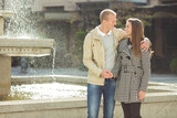 Portrait of happy young couple embracing in front of the fountain in the city centre