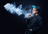 hipster woman with blue hair smoking vape on black background. Copy space