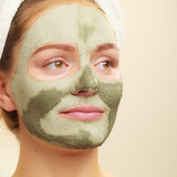 Woman face with green clay mud mask - 136334300
