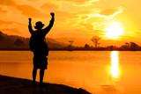 Traveler man with backpack hands raised sunset landscape.