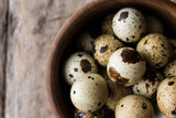 quail eggs on bowl on wood - top view