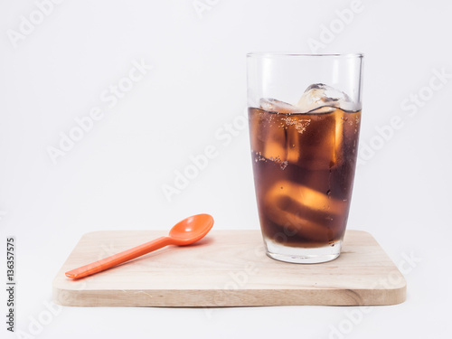 two of thirds soft drink is cool and ice cubes in glass near orange spoon on woo Poster