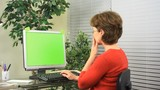 A woman sitting in front of a computer displays excitement about what she sees on her monitor. monitor green screen for your own use