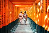 Japanese woman in kimono dress among red wooden Tori Gate at Fushimi Inari Shrine in Kyoto, Japan