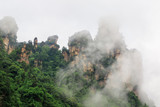 Photo of Huge Rock Mountains Surrounded by Green Trees and White Mist Clouds. Epic Mountain Landscape