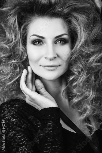 Model with blonde long hair in guipure clothing. Waves Curls Hairstyle. Fashion model with shiny hair. Woman with healthy hair. Girl with luxurious haircut and hair volume © oksana_bondar