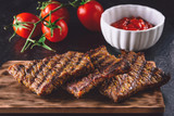 Sliced grilled meat, barbecue, grilled beef on wooden board on black background with fresh tomatoes and sauce