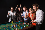 Group of young people behind roulette table on black background