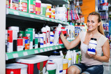 Glad woman customer looking for paint solvent in bottle