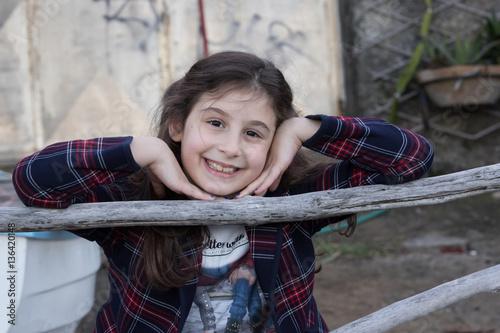 Poster Il sorriso della bambina con le mani sul viso