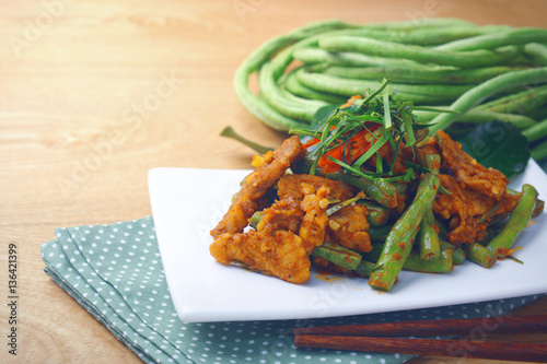 Poster stir fried pork curry lentils on white plate with fresh green sting bean at background