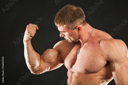 Big muscles man showing biceps. Bodybuilder at studio