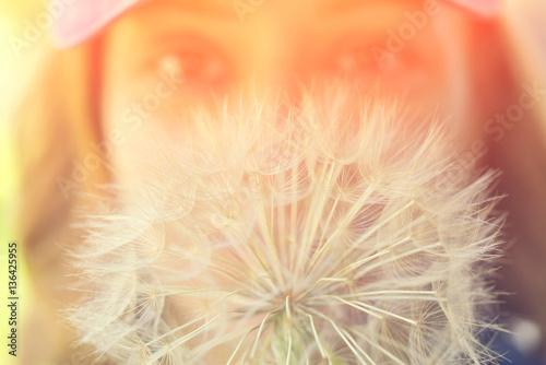 Portrait of a beautiful woman with big dandelion