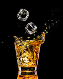 Glass of whiskey with splash on black background - 136432302