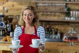 Portrait of smiling waitress offering cup of coffee
