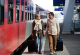 Senior couple on train station pulling trolley luggage.