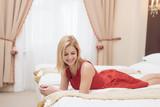 Beautiful woman in red dress posing in elegant hotel room