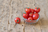 Cherry tomatoes in a bowl of glass on a rustic table.