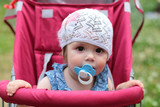 Frontal view of a cute baby girl with a soother in her mouth. Li