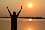Woman put hand up beside lake under the sky and sun evening