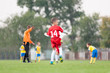 Young soccer player in red jersey on the football field