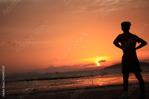 Poster sagoma uomo guarda il tramonto sulla spiaggia