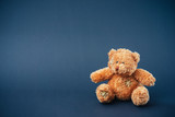Teddy bear on dark blue background, empty space, postcard
