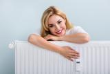 Woman In Sweater Leaning On Radiator - 136508563