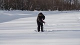 The fisherman on the river drills ice