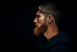 Fototapety Close-up image of serious brutal bearded man on dark background