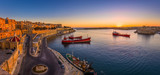 Valletta, Malta - Panoramic shot of an amazing summer sunrise at Valletta's Grand Harbor with ships and the ancient houses and walls of the maltese capital city.