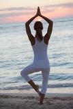 femme sur la plage le soir qui fait du yoga