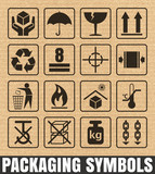 Packaging symbols on cardboard background including Fragile, Handle with care, Keep dry, This side up, Flammable, Recycled, Package weight, Do not litter, Max stack, Clamp and Sling here, and others