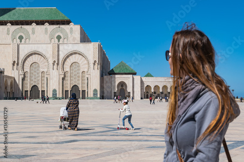 Tourist outside Hassan II Mosque in Casablanca, Morocco. Poster
