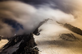 Long exposure shoot of a high mountain peak covered with fast moving clouds