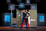 actress brunette woman in a sexual way, and a man in a blue suit an actor playing the role in the play on the background of a theater stage with decorations