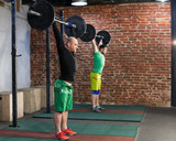 Two men are training at the gym, lifting up the barbells