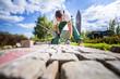 Handwerker verlegt Pflastersteine in einer Gartenanlage
