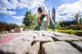 Handwerker verlegt Pflastersteine in einer Gartenanlage  - 136552359