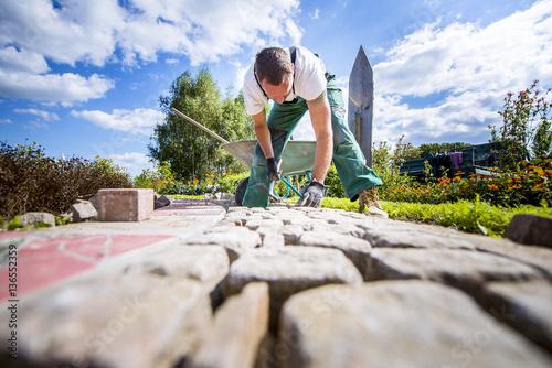 Handwerker verlegt Pflastersteine in einer Gartenanlage Poster