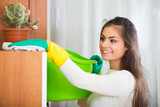 Woman in jersey cleaning furniture