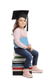 Little girl with graduation hat sitting on pile of books
